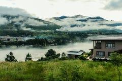 Pueblo butanés cerca del río en un día de niebla en Punakha, Bhután Foto de archivo