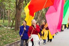 Pueblo chino que celebra marchar colorido de las banderas Fotografía de archivo
