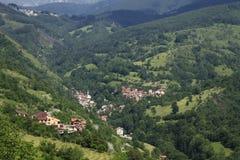 Pueblo con las casas cubiertas rojas en las montañas enselvadas en Kosovo Foto de archivo
