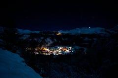 Pueblo de la iluminación en las montañas en la noche, nieve Imagenes de archivo