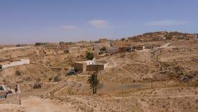 Pueblo de los beduinos de la visión panorámica en desierto del Sáhara Pueblo del Berber en desierto salvaje metrajes