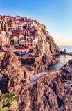 Pueblo, rocas y mar de Manarola en la puesta del sol. Cinque Terre, Italia Foto de archivo libre de regalías