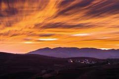 Pueblo de montaña bajo resplandor de la puesta del sol Imagen de archivo libre de regalías