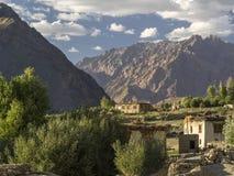 Pueblo de montaña: las casas pobres de un piso blancas colocan las altas rocas marrones medias, porciones de árboles verdes, vera Foto de archivo libre de regalías