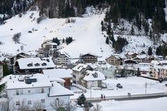 Pueblo de montaña nevado en el pie de la montaña por tarde del invierno, montañas de Ischgl el Tyrol de la estación de esquí Fotografía de archivo libre de regalías