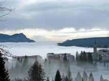 Pueblo de montaña rodeado por la niebla densa Foto de archivo libre de regalías