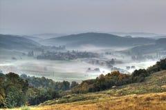Pueblo de montaña rural en la opinión aérea de la niebla Foto de archivo