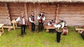 Pueblo de Nahuievychi, Lviv, Ucrania - 26 de agosto de 2018: Los hombres en vestido nacional ucraniano tocan los instrumentos mus almacen de video