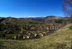 Pueblo de Simon y montañas de Piatra Craiului Foto de archivo libre de regalías
