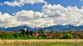 Pueblo de Transilvania en Rumania, en la primavera con las montañas en el fondo Fotos de archivo