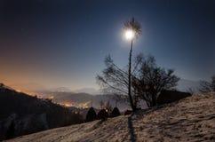 Pueblo debajo de la montaña en la noche con la luna Imagen de archivo