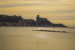 Pueblo del castillo del mar en la puesta del sol Fotos de archivo libres de regalías