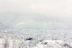 Pueblo en las colinas del bosque cubiertas con nieve Foto de archivo