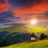 Pueblo en prado de la ladera con el bosque en la puesta del sol imagen de archivo