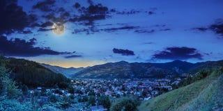 Pueblo en prado de la ladera con el bosque en montaña en la noche foto de archivo libre de regalías