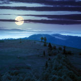 Pueblo en prado de la ladera con el bosque en montaña en la noche Foto de archivo