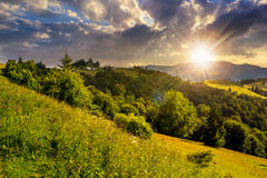 Pueblo en prado de la ladera con el bosque en montaña en la puesta del sol Fotos de archivo libres de regalías