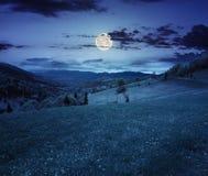 Pueblo en prado de la ladera en la noche foto de archivo libre de regalías