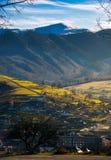 Pueblo en valle montaña distante con el top nevoso foto de archivo