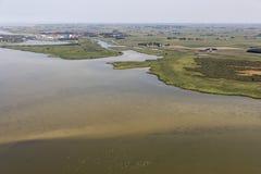 Pueblo holandés Makkum de la visión aérea en el lago IJsselmeer con el agua poco profunda imagen de archivo