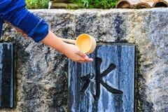 Pueblo japonés no identificado que lava la mano en la fuente antes de dar la adoración Fotografía de archivo