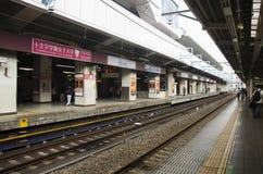 Pueblo japonés y tren y subterráneo que esperan del viajero del extranjero Fotos de archivo libres de regalías
