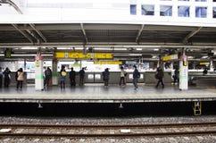 Pueblo japonés y tren y subterráneo que esperan del viajero del extranjero Fotos de archivo