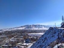 pueblo ocultado entre las montañas en invierno imagen de archivo libre de regalías