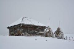 Pueblo rumano tradicional viejo con dos pajares el invierno Fotografía de archivo libre de regalías