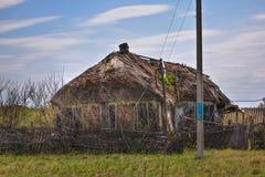 Pueblo ruso abandonado Ruinas de la casa rural con el tejado cubierto con paja Foto de archivo libre de regalías