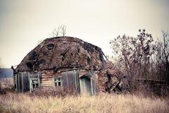 Pueblo ruso abandonado Ruinas de la casa rural con el tejado cubierto con paja Fotos de archivo libres de regalías