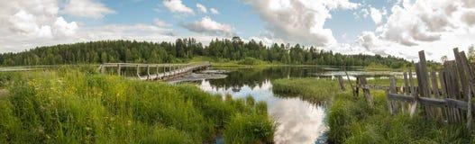 Pueblo ruso del norte Isady Día de verano, río de Emca, cabañas viejas en la orilla, puente de madera viejo y reflexiones de las  fotos de archivo