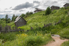 Pueblo ruso del norte Isady Día de verano, río de Emca, cabañas viejas en la orilla, puente de madera viejo y reflexiones de las  fotos de archivo libres de regalías