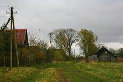 Pueblo ruso por la hierba verde, gris azul, cielo nublado de Orthern Imagenes de archivo