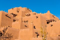 Multi-story pueblo style adobe building in Santa Fe, New Mexico. Pueblo style adobe building in Santa Fe, New Mexico in warm evening light under a bright blue royalty free stock images
