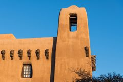 Pueblo style adobe building and tower with rustic beams in Santa Fe, New Mexico. Historic pueblo style adobe building and tower with rustic beams and a window in stock photography
