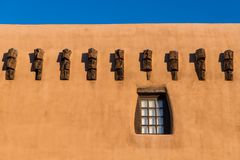 Pueblo style adobe building wall and rustic wood-framed window and beams in Santa Fe, New Mexico stock photos