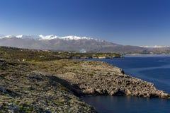 Pueblo tradicional cerca del mar con las montañas nevosas y el cielo azul en fondo crete imagenes de archivo