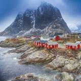 Pueblo tradicional de la choza de la pesca en pico de montaña de Hamnoy en las islas de Lofoten, Noruega Foto de archivo