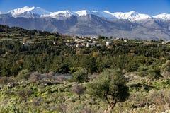 Pueblo tradicional en montaña con las montañas nevosas y el cielo azul en fondo crete fotografía de archivo libre de regalías
