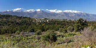 Pueblo tradicional en montaña con las montañas nevosas y el cielo azul en fondo crete fotos de archivo libres de regalías