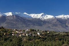 Pueblo tradicional en montaña con las montañas nevosas y el cielo azul en fondo crete foto de archivo