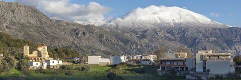 Pueblo tradicional en montaña con las montañas nevosas y el cielo azul en fondo crete imagen de archivo libre de regalías