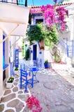 Pueblo tradicional griego típico en verano con las paredes blancas, los muebles azules y el bougainvilla colorido, isla de Skiatho Foto de archivo