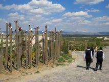 Pueblo Uchisar Muestra del valle de la paloma Tres hombres en trajes negros y camisas blancas están caminando a lo largo del cami fotografía de archivo libre de regalías
