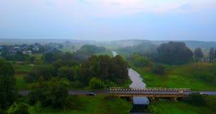Pueblo ucraniano en la niebla, el coche en el puente Vuelo del abejón