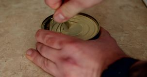 Pueda abierto con los pescados de la sardina en el primer del aceite de fingeres y del abrelatas del metal almacen de video