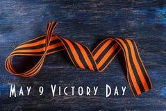 9 pueden día de la victoria Cinta de San Jorge en un fondo de madera Fotos de archivo