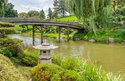 Puente al área japonesa del jardín con la linterna de la piedra del estilo japonés en frente Foto de archivo