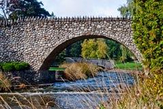 Puente arqueado hecho de piedras irregulares Fotografía de archivo libre de regalías